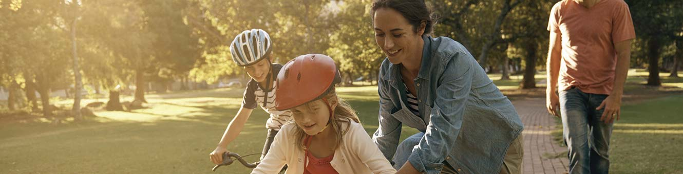 Father and mother teaching their children to ride bikes.